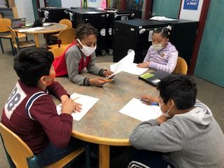 Group of 4 elementary math students at a table solving math problems