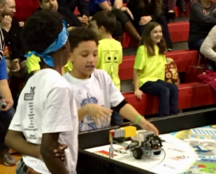 Blossomwood students set up their LEGO robot on the competition board.