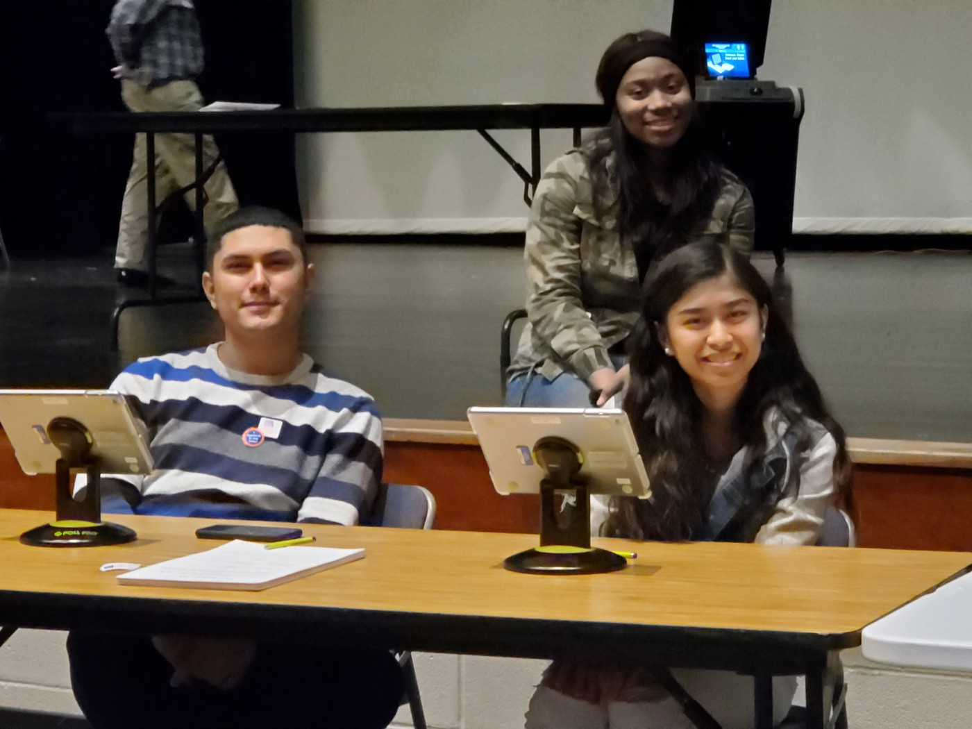 Three students sitting at the Polling Station for Mock Election in front of stage at Columbia High School