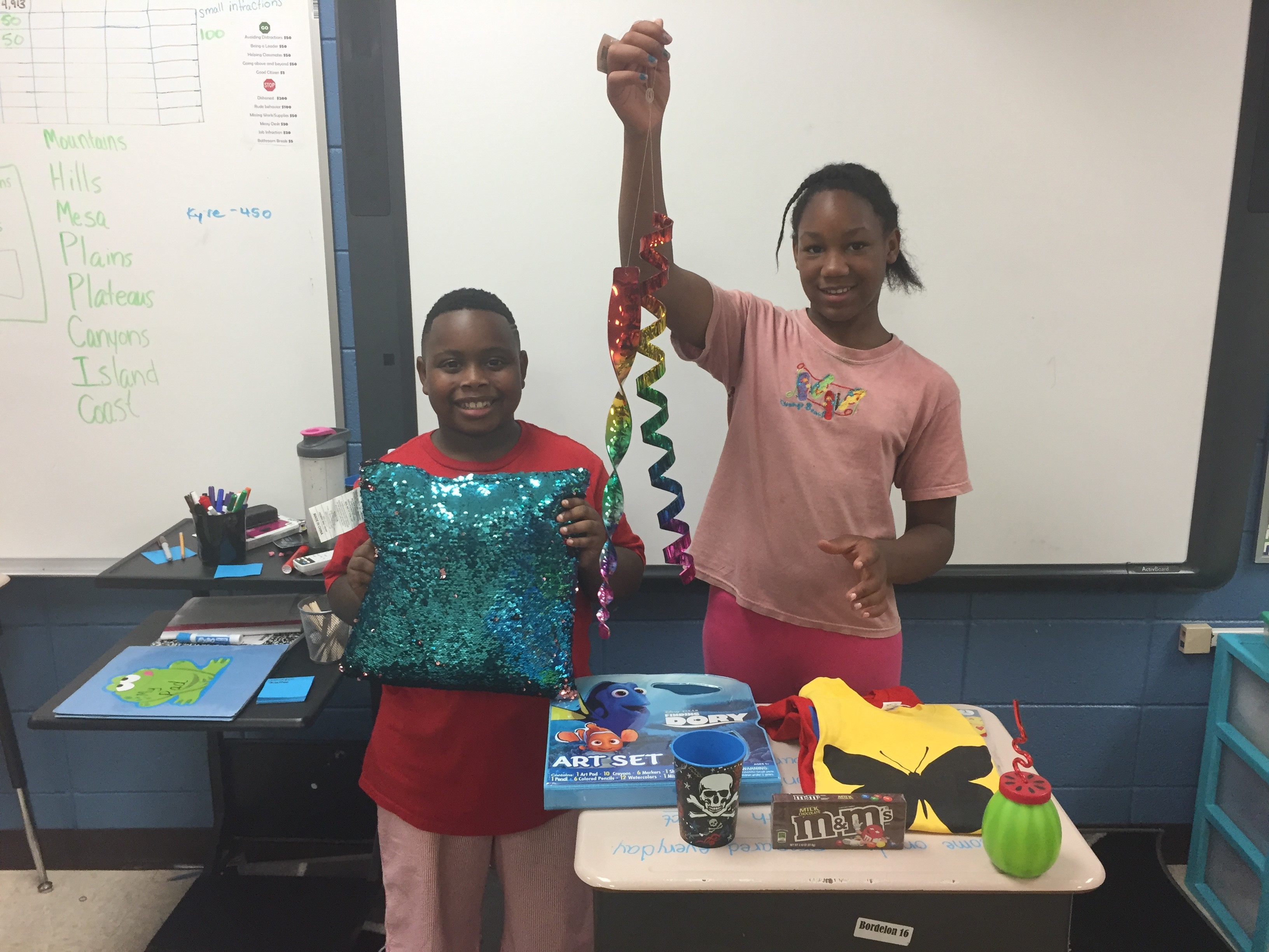 Two students in Miss Upp's 4th grade class display some of their auction prizes