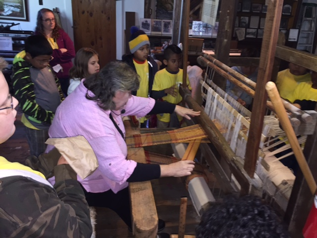 Students watching weaving demonstration at Falls Mill