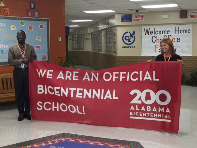 Mr. Walker and Mrs. Nelson holding Bicentennial banner