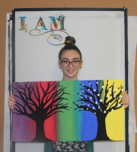 Sophomore, Hannah Szcepanski displaying two of her paintings.