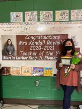 """2020 Teacher of the Year, Mrs. Kendall Reynolds, posing with her Teacher of the Year Award in front of a congratulatory banner that reads """"Congratulations Mrs. Kendall Reynolds 2020-2021 Teacher of the Year Martin Luther King Jr. Elementary"""""""