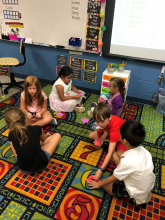 2nd Grade students sitting on a carpet in the floor of the classroom working on a reading center