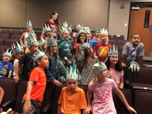 2nd grade students wearing Lady Liberty crowns posing for a picture with Lady Liberty at the assembly program.