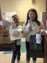 Two 3rd grade students holding their passport bags