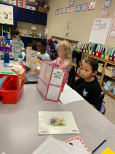 3rd grade students sit at desks using their writing office folders while working through the writing process