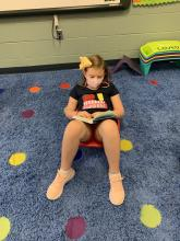 Student sitting on carpet reading a book