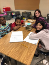 4th Grade students sitting at desks with notebooks observing frog
