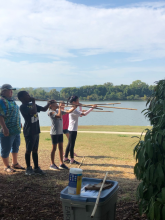 4th Grade students standing next to water holding spears and practicing blowing darts