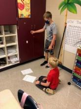 Two students standing by cabinet measuring energy from ball being dropped
