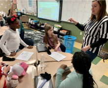 A 4th grade teacher instructs students during their super bowl math challenge.
