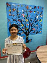 Anna holding her certificate after winning the spelling bee!