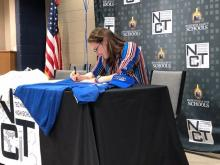 Ann Lawrence Hampton smiles as she signs with UAH accepting a scholarship for track and field - pole vaulting.