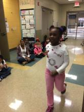 "A second grader walks the ""runway"" wearing her 100th day t-shirt."