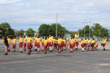 Columbia High School band members standing in the parking lot at Milton Frank stadium wearing yellow shirts with crimson colored C's on them