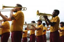 Columbia High School band members playing the trombone wearing yellow shirts with crimson colored C's on them