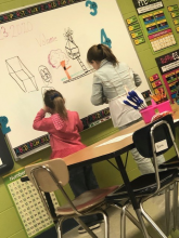 Two students standing in front of the white board working on solving volume problems of various shapes