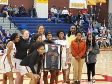 Senior Basketball girl student holding up framed jersey wit the girls basketball team standing around her in CHS gym