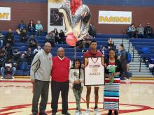 Basketball Senior Geraldo holds up framed jersey in the middle with Coach, his father, his sister on left and mother stands on right of him