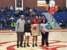 Basketball Senior player Cortez holds up framed jersey in the gym with Coach and sister on his left and his mother standing on his right