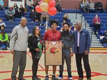 Basketball Senior Justin holds up framed jersey in the middle with Coach, his mother on left, his brother and father stand on right of him