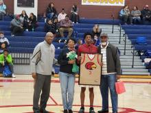 Basketball Senior Kovi holds up framed jersey in the middle with Coach, his mother on left and father stand on right of him