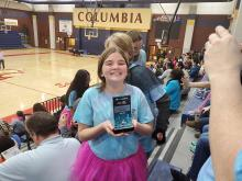 A Blossomwood student holds their trophy from the First Lego League Competition