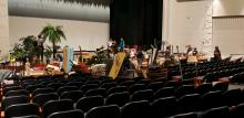 Students from IB, Robotics and Theatre organizing equipment, props in the auditorium