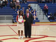 Girl cheerleader standing  and holding a bouquet of flowers in the gym during senior night with her father