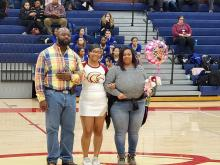 Senior Cheerleader standing in the middle arm and arm with her father on the left and her mom on the right holding balloon, bouquet of flowers and card