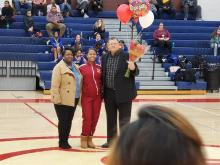 Senior Cheerleader standing in the middle with her mom on the left and her dad on the right holding up a bouquet of flowers and balloons