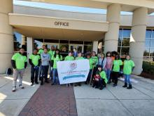 Columbia High School students and members of the Clean Home Alabama Project hold up sign in front of the school.