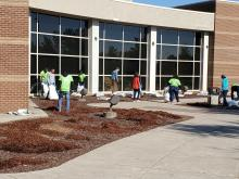 Clean Home Alabama Project Members and Columbia High School students cleaning in front of the building.