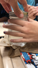Glass Mason jar with homemade cloud sitting on wet paper towels while being held by hands of 5th grade students