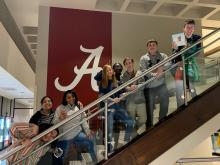 IB French students from Columbia High School standing on stairwell at the University of Alabama in Tuscaloosa after performing song in French