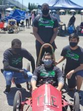The Columbia High School's Green Power Team standing around team member in electric car on the race track