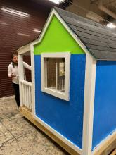IB student painting blue and green  playhouse for the Habitat for Humanity Project