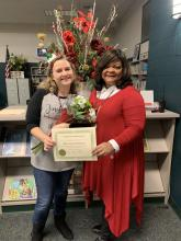 Mrs. Harbour and Principal Ashley in library presenting Mrs. Harbour with a certificate and flowers