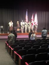 Assistant Principal and counselor standing on the stage with the Eagle Battalion holding flags during the awards day ceremony with parents sitting in the auditorium facing the stage