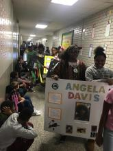 """MLK students sitting in hall observing other students participating in a parade while holding a poster with the name Angela Davis and photos on it."""