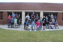 Junior and senior engineering students posing together in the school courtyard.