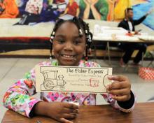 Montview student smiling while holding her ticket to the Polar Express party