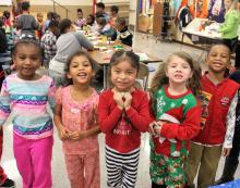 Five kindergarten students smiling at the Polar Express party