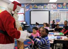 Santa giving a candy can to a 2nd grader