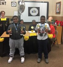 Spelling bee 2nd place winner, Talen Adams, and 1st place winner, Philip McCrimon, holding their trophies and balloons