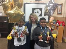 Spelling bee 1st and 2nd place winners posing for a picture with Principal Marcia Sutton