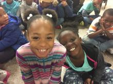 Two girls smiling for the camera at the Montview holiday sing-along