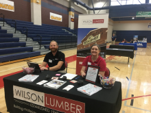 Two employers from Wilson Lumber sitting at a table set up with supplies waiting to speak to the students at Columbia High School